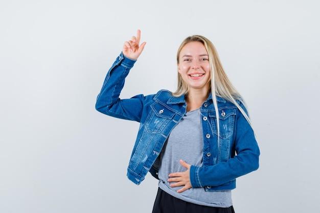 T- 셔츠, 데님 재킷, 스커트를 가리키는 매력적인 젊은 아가씨