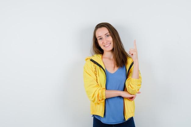 Tシャツ、ジャケットを着て、自信を持って見ている若い女性。正面図。