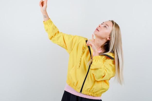 Tシャツ、ジャケットで上向きに焦点を当てている若い女性