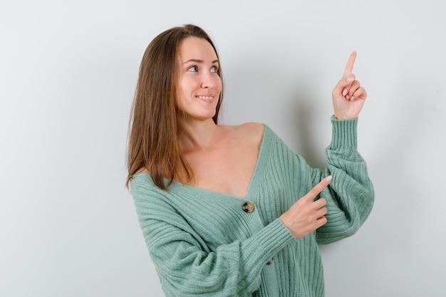ウールのカーディガンで上向きで元気そうな若い女性。正面図。