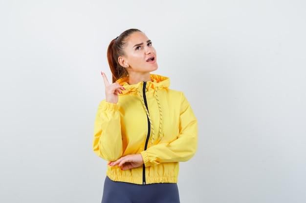 Giovane donna che punta verso l'alto, aprendo la bocca in giacca gialla e guardando stupita. vista frontale.