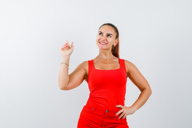 Young lady pointing up in red singlet, red trousers and looking cheery. front view.