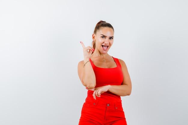 Giovane donna rivolta verso l'alto in canottiera rossa, pantaloni rossi e gioiosa, vista frontale.