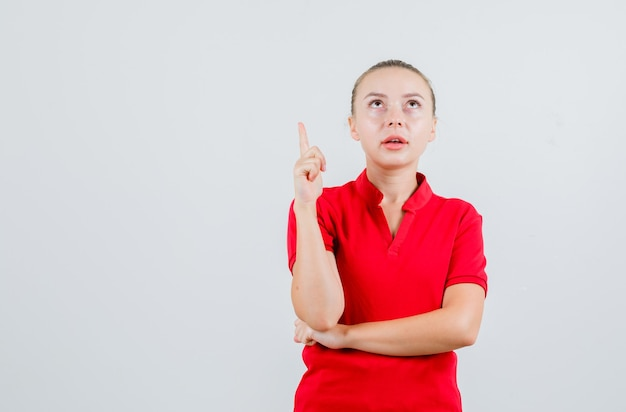 Young lady pointing up in red t-shirt and looking focused