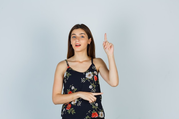 Giovane donna che indica in alto e a destra in camicetta e sembra meravigliata. vista frontale.