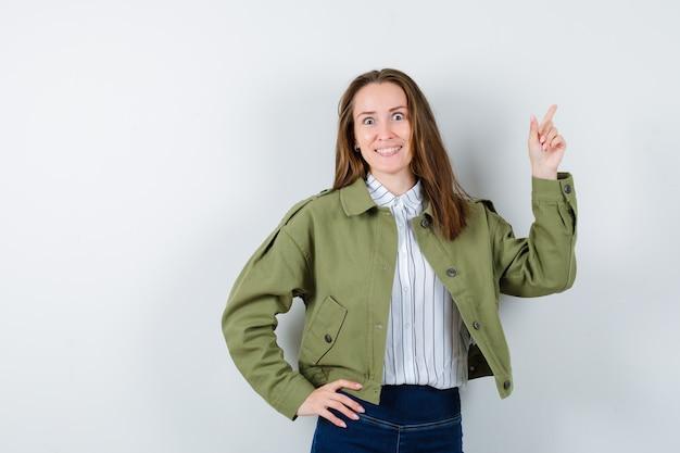 Giovane donna che punta in camicia, giacca e sembra felice, vista frontale.
