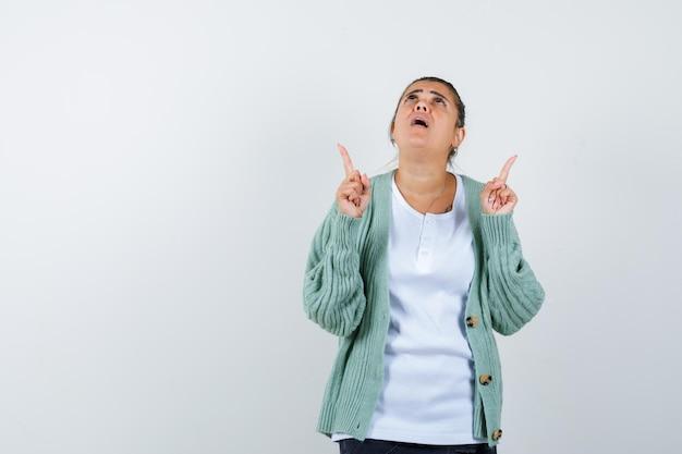 Giovane donna che indica in t-shirt, giacca e sembra stupita