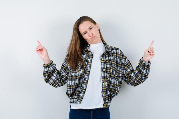 Giovane donna che indica in su in maglietta, giacca e sembra senza speranza. vista frontale.