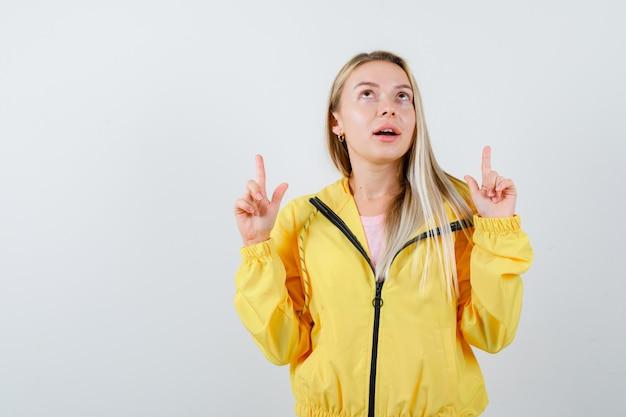 Giovane donna rivolta verso l'alto in t-shirt, giacca e sguardo perplesso