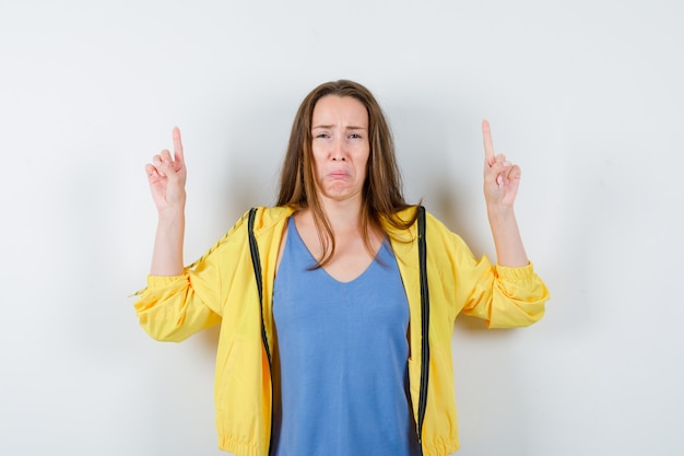 Giovane donna che indica in t-shirt, giacca e sembra triste, vista frontale.