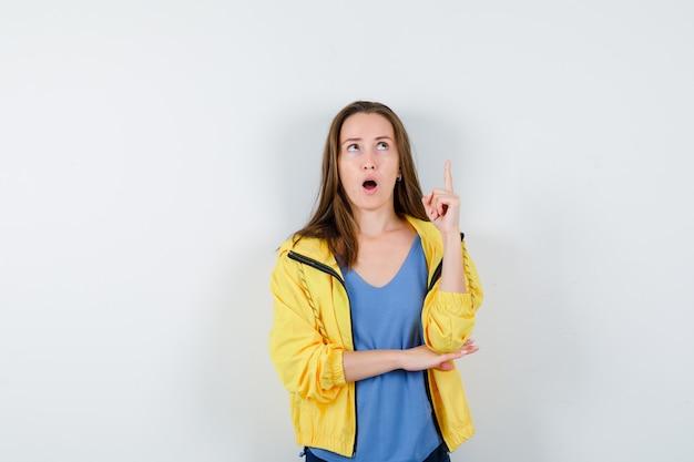 Giovane donna che punta in t-shirt, giacca e sembra sorpresa, vista frontale.