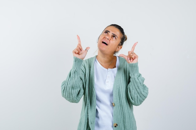 Giovane donna che indica in t-shirt, giacca e sembra pensierosa