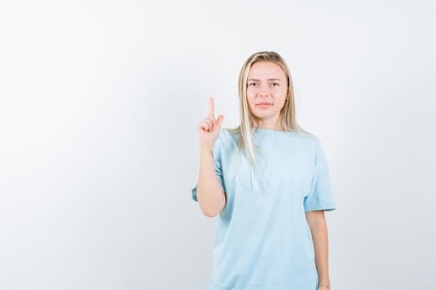 Giovane signora che indica in su in maglietta e che sembra sicura. vista frontale.