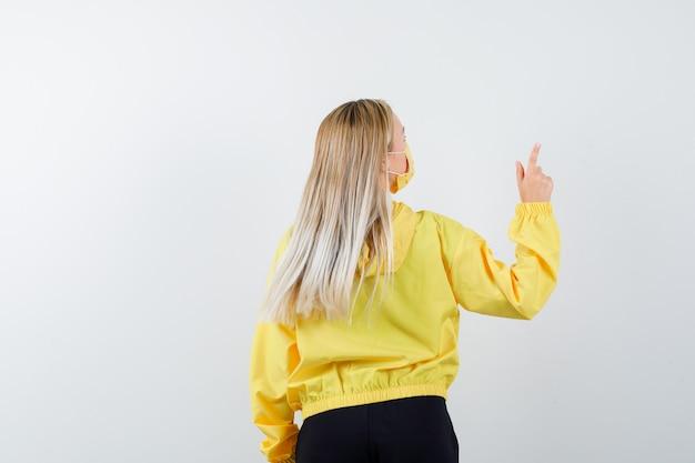 Giovane donna rivolta verso l'alto in tuta da ginnastica, maschera e guardando concentrato, vista posteriore.