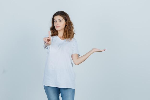 Tシャツ、ジーンズに何かを持って自信を持って見ながら上向きの若い女性。正面図。