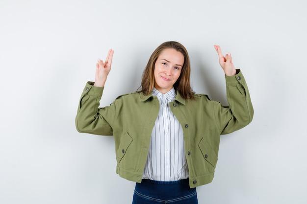 シャツ、ジャケット、自信を持って見える手と2本の指で上向きの若い女性。正面図。