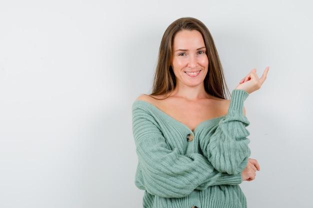 Giovane donna rivolta verso l'alto in cardigan di lana e guardando felice. vista frontale.