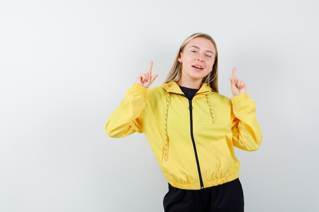 Young lady pointing up in yellow jacket, pants and looking merry. front view.