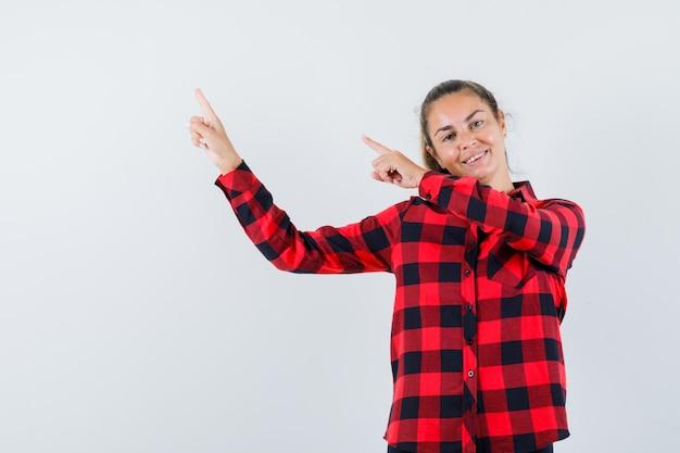 Giovane donna che punta all'angolo superiore sinistro in camicia a quadri e sembra allegra