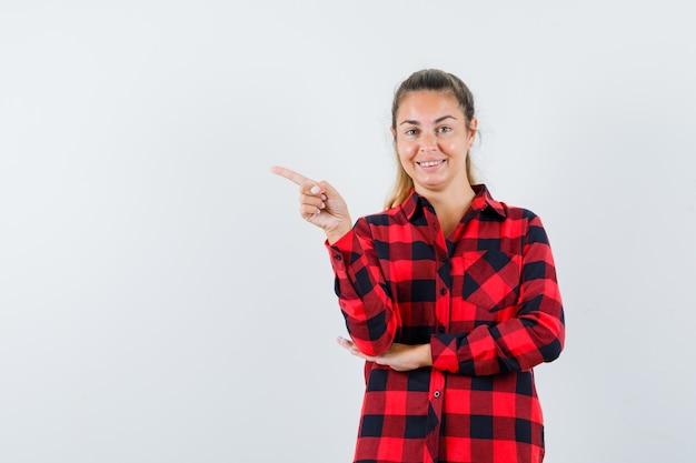 Giovane donna che punta all'angolo in alto a sinistra in camicia a quadri e sembra allegra