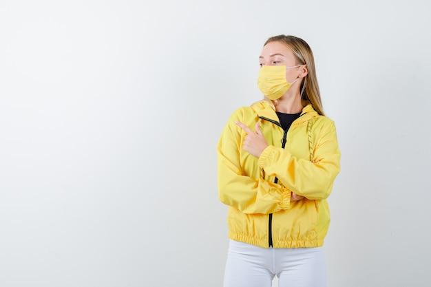 Giovane donna che punta all'angolo in alto a sinistra in giacca, pantaloni, maschera e sembra sicura. vista frontale.