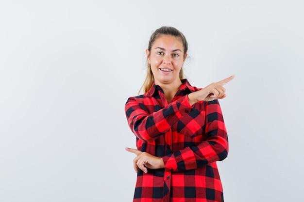 Giovane donna che punta all'angolo in alto a destra in camicia a quadri e sembra allegra