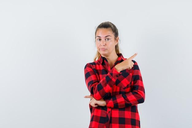 Giovane donna che punta all'angolo in alto a destra in camicia a quadri e sembra esitante
