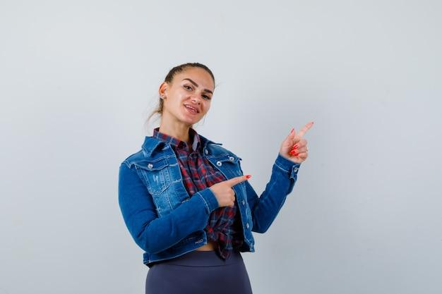 Giovane donna che punta all'angolo in alto a destra in camicia, giacca e sembra felice, vista frontale.