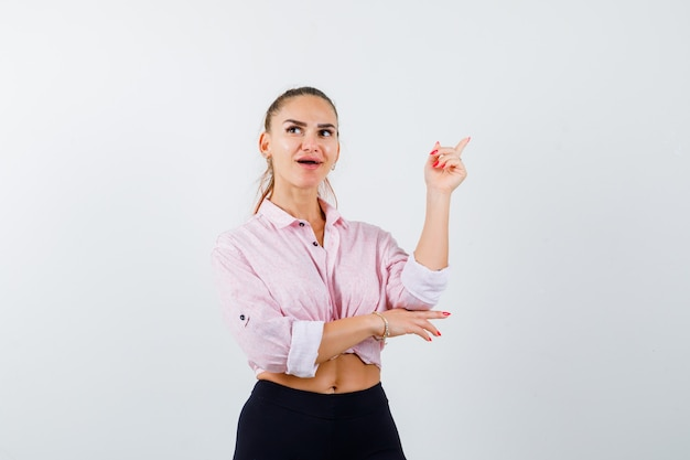 Young lady pointing at upper right corner in shirt, pants and looking amazed. front view.
