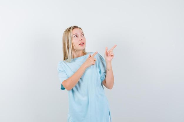 Giovane donna che indica nell'angolo in alto a destra in maglietta e sembra sicura isolata