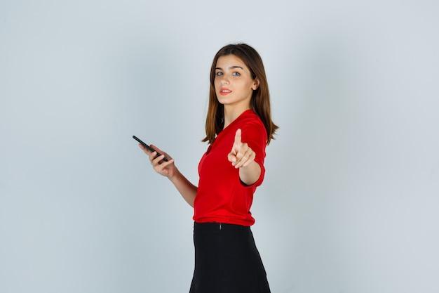 Giovane donna che indica mentre si tiene il telefono cellulare in camicetta rossa, gonna e sembra sicura