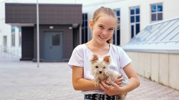 Young lady poses with dog on street. teenage girl in white t-shirt holds small puppy in arms and looks straight smiling by city buildings close view