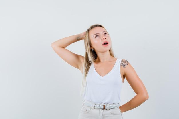 白いブラウスでカメラにポーズをとって印象的な若い女性