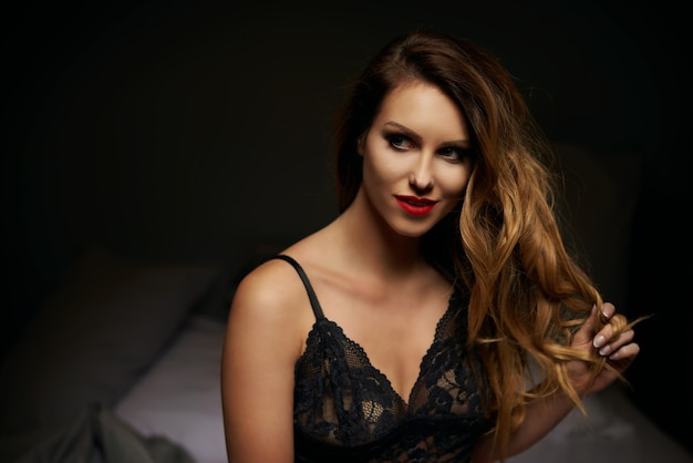 ベッドでポーズをとる若い女性