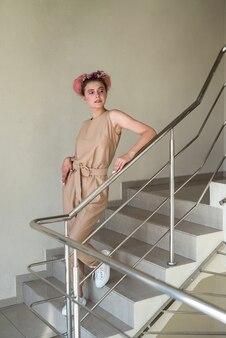 フルサイズの建物内の階段でポーズをとる若い女性