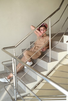 Young lady posing on the stairs inside building full size