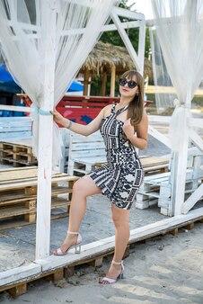 Young lady posing at summer time near lake at white gazebo