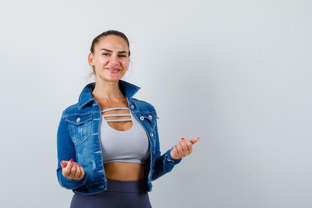 Giovane donna in posa in alto, giacca di jeans e guardando gioiosa, vista frontale.