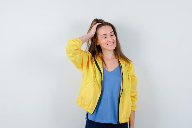Giovane donna in posa mentre si pettina i capelli con la mano in maglietta, giacca e guarda le vertigini, vista frontale.