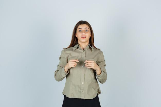 셔츠, 치마에 카메라를보고 당황한 찾고있는 동안 포즈를 취하는 젊은 아가씨