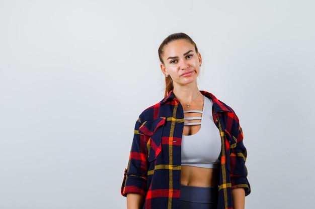 Молодая леди позирует, глядя в камеру в верхней, клетчатой рубашке и осторожно. передний план.