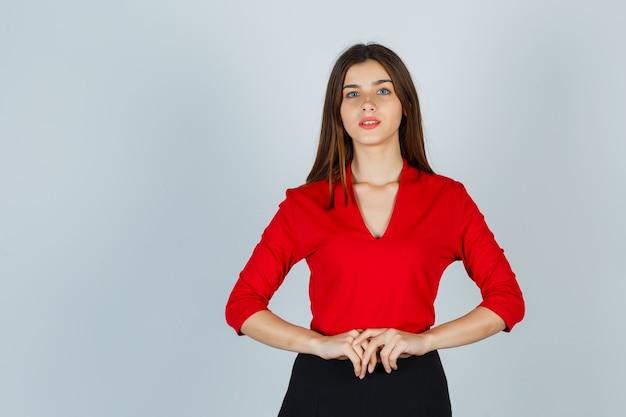 Giovane donna in posa mentre guarda la telecamera in camicetta rossa, gonna e sguardo concentrato