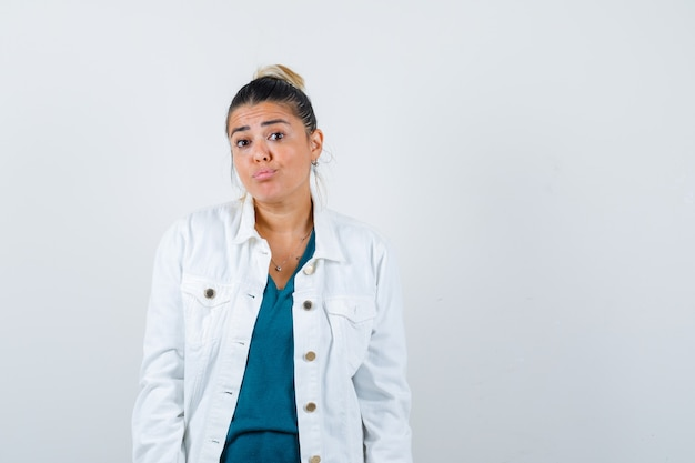셔츠, 흰색 재킷을 입고 조심스럽게 바라보면서 포즈를 취하는 젊은 아가씨. 전면보기.