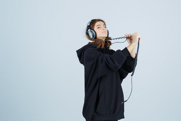 Giovane donna in posa mentre si tira handphones in felpa con cappuccio oversize, pantaloni e sembra divertente, vista frontale.