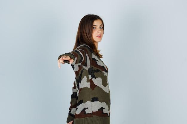 Giovane donna in posa mentre scetching mano in maglione e sembra fresca