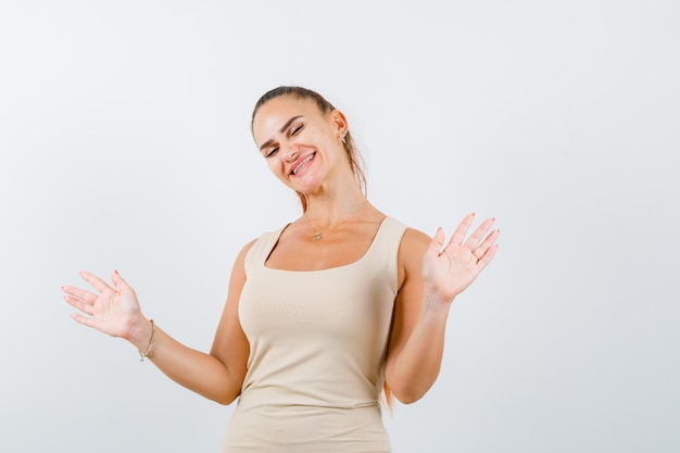 Young lady posing while showing palms in beige tank top and looking cheerful , front view.