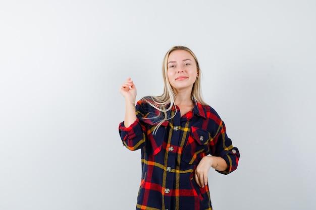 Giovane donna in posa mentre in piedi in camicia a quadri e sembra attraente, vista frontale.