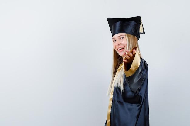 Молодая дама позирует, стоя в академической одежде и выглядит счастливой.