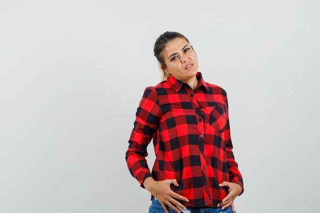 チェックシャツ、ショートパンツに立って華やかに見えながらポーズをとるお嬢様。