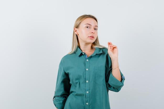 緑のシャツに立って、賢明に見えながらポーズをとる若い女性。